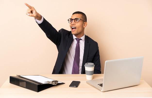 Jonge zakenman in zijn kantoor met een laptop en andere documenten die weg wijzen