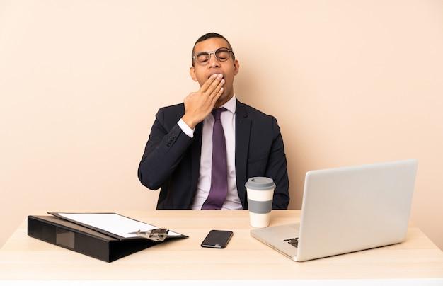 Jonge zakenman in zijn kantoor met een laptop en andere documenten geeuwen