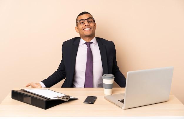Jonge zakenman in zijn kantoor met een laptop en andere documenten glimlachen