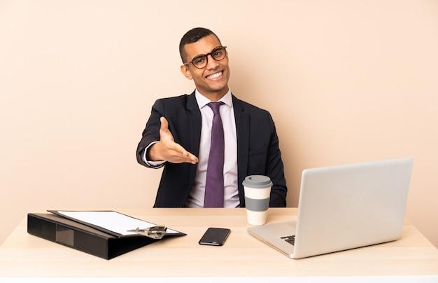 Jonge zakenman in zijn kantoor met een laptop en andere documenten handen schudden voor het sluiten van een goede deal