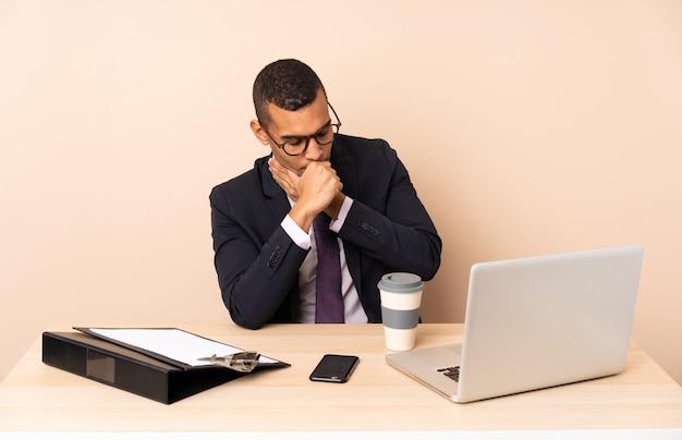 Jonge zakenman in zijn kantoor met een laptop en andere documenten lijdt aan hoest en voelt zich slecht