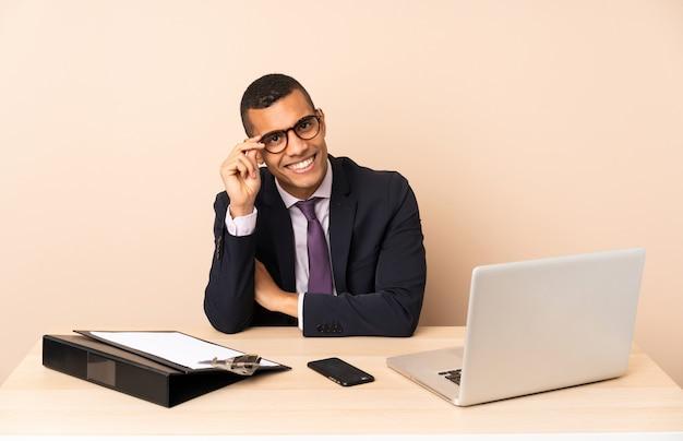 Jonge zakenman in zijn kantoor met een laptop en andere documenten met een bril en gelukkig