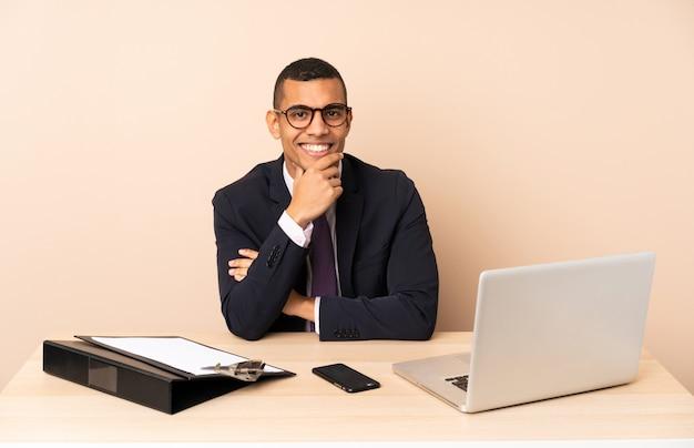 Jonge zakenman in zijn kantoor met een laptop en andere documenten met een bril en glimlachen