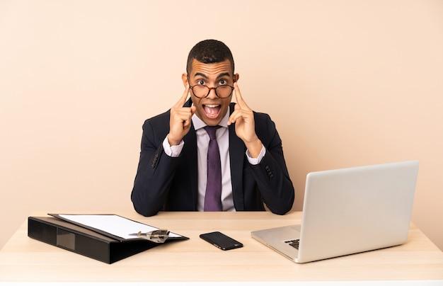Jonge zakenman in zijn kantoor met een laptop en andere documenten met een bril en verrast