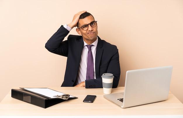 Jonge zakenman in zijn kantoor met een laptop en andere documenten met een uitdrukking van frustratie en niet begripvol