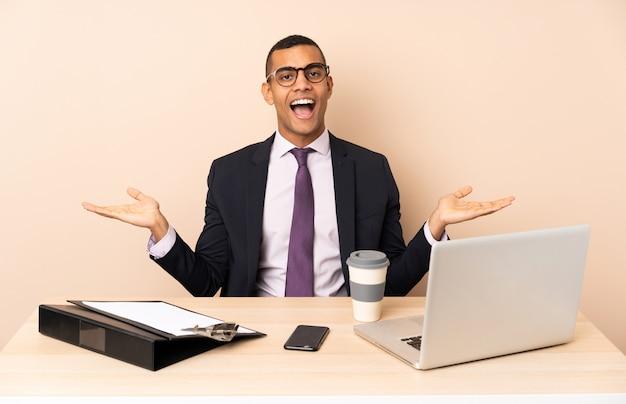 Jonge zakenman in zijn kantoor met een laptop en andere documenten met geschokte gelaatsuitdrukking