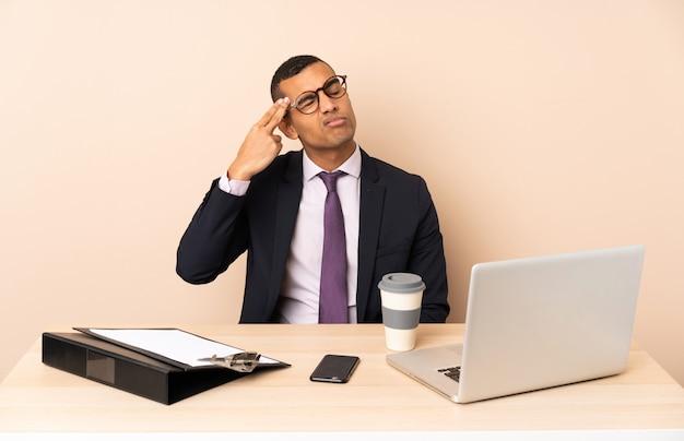 Jonge zakenman in zijn kantoor met een laptop en andere documenten met problemen die zelfmoordgebaar maken