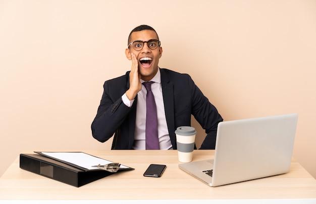 Jonge zakenman in zijn kantoor met een laptop en andere documenten met verrassing en geschokte gelaatsuitdrukking