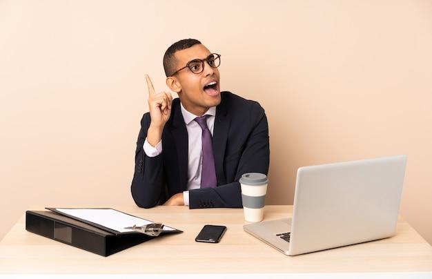 Jonge zakenman in zijn kantoor met een laptop en andere documenten van plan om de oplossing te realiseren terwijl hij een vinger opheft