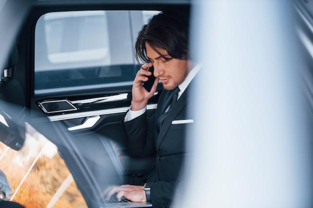 Jonge zakenman in zwart pak en stropdas in moderne auto.