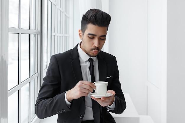 Jonge zakenman in zwart pak zit en drinkt warme koffie.