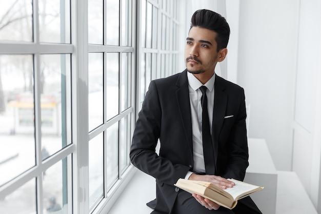 Jonge zakenman in zwart pak zit en leest een boek en kijkt op het raam