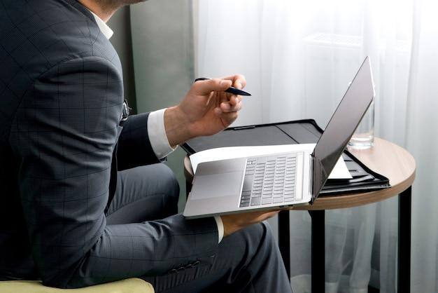 Jonge zakenman is met behulp van laptop en werken met documenten zittend in de hotelkamer met koffer.