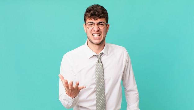 Jonge zakenman kijkt boos, geïrriteerd en gefrustreerd schreeuwend wtf of wat is er mis met jou?