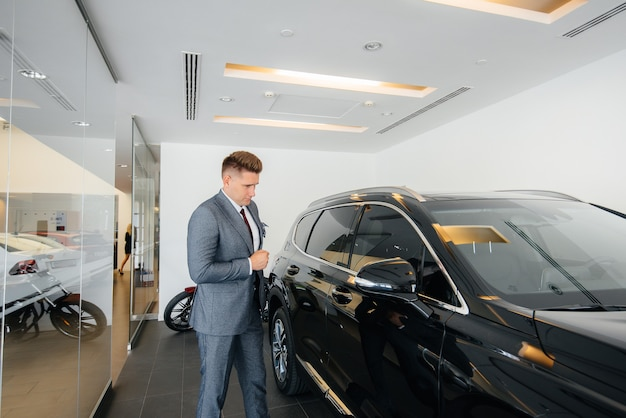 Jonge zakenman kijkt naar een nieuwe auto in een autodealer