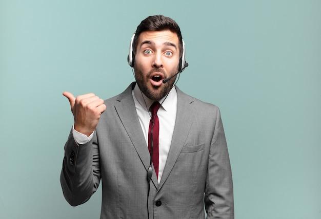 Jonge zakenman kijkt verbaasd in ongeloof, wijst naar een object aan de zijkant en zegt wow