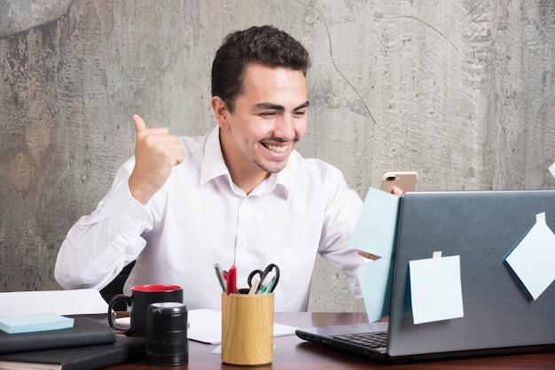 Jonge zakenman kreeg blij nieuws aan het bureau.