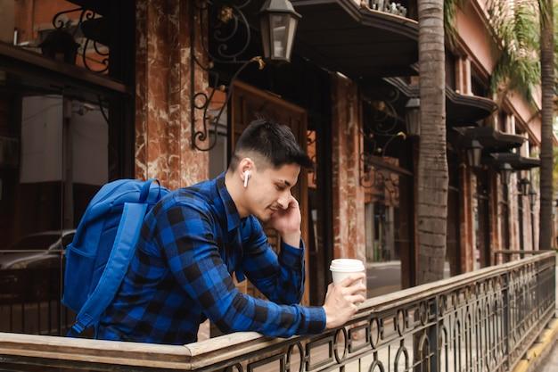 Jonge zakenman leunend bij een bar, luisteren naar muziek op zijn draadloze koptelefoon en koffie drinken.