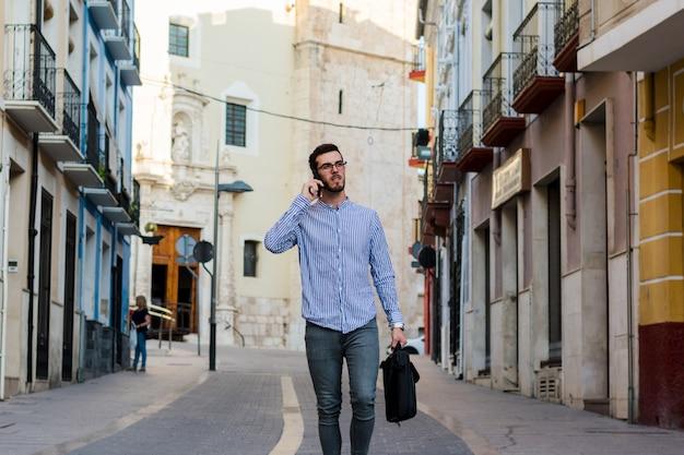 Jonge zakenman loopt op straat terwijl hij met zijn telefoon spreekt