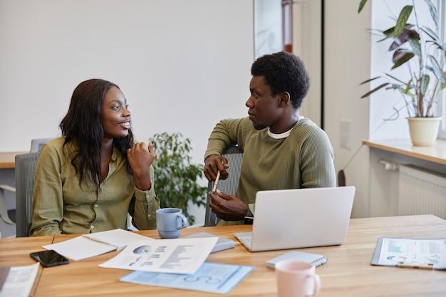 Jonge zakenman luisteren naar lachende collega praten over haar succesvolle zakelijke project