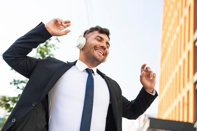 Jonge zakenman luisteren naar muziek en dansen