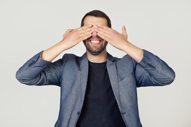 Jonge zakenman man met een baard in een jas die zijn ogen bedekt met zijn handen glimlachend vrolijk en grappig.