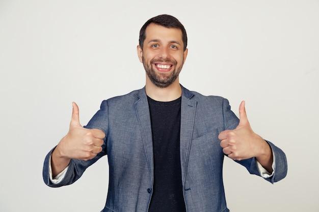 Jonge zakenman man met een baard in een jas, een teken van succes maakt een positief gebaar met zijn hand, duimschroef opwaarts glimlachend en blij.