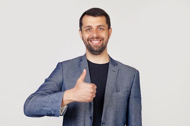 Jonge zakenman man met een baard in een jas, met een gelukkige glimlach, toont zijn duim