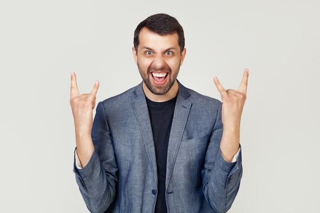 Jonge zakenman man met een baard in een jas, schreeuwend met een gekke uitdrukking op zijn gezicht, een rotssymbool maken met zijn handen omhoog.