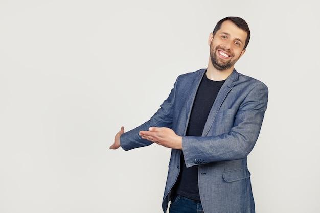 Jonge zakenman man met een baard in een jasje, uitnodigend om binnen te komen, natuurlijk glimlachend met een open hand. portret van een man op een grijze achtergrond.