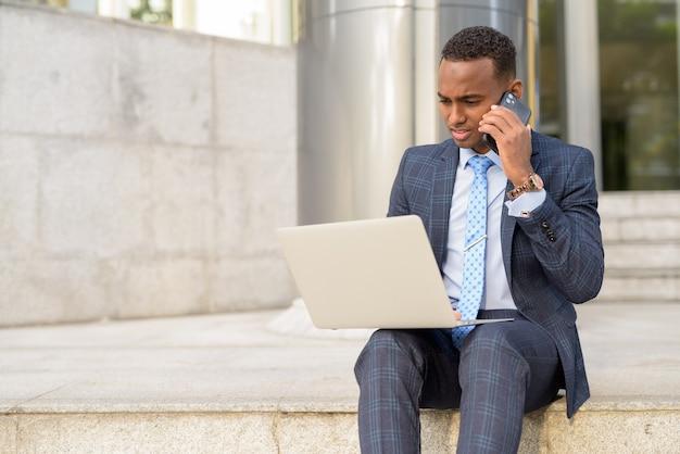 Jonge zakenman met behulp van laptop en praten aan de telefoon door de trap buitenshuis