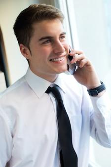 Jonge zakenman met behulp van zijn mobiele telefoon in kantoor.