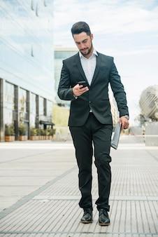 Jonge zakenman met behulp van zijn telefoon tijdens het lopen op de stoep in de campus