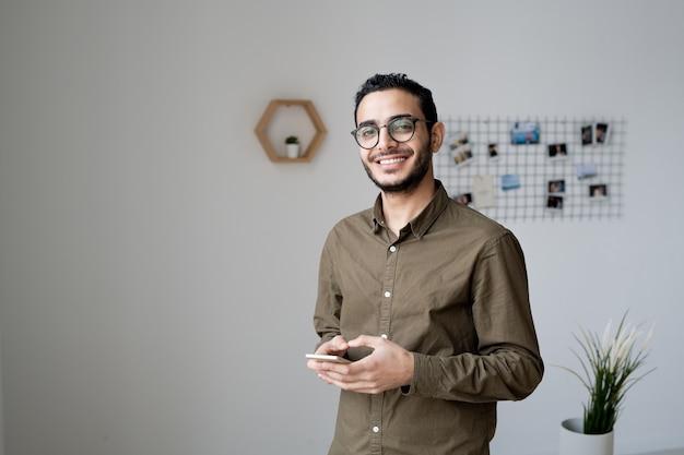 Jonge zakenman met brede glimlach scrollen in smartphone terwijl staande voor camera in kantoor