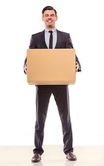 Jonge zakenman met doos om naar een nieuw kantoor te verhuizen.