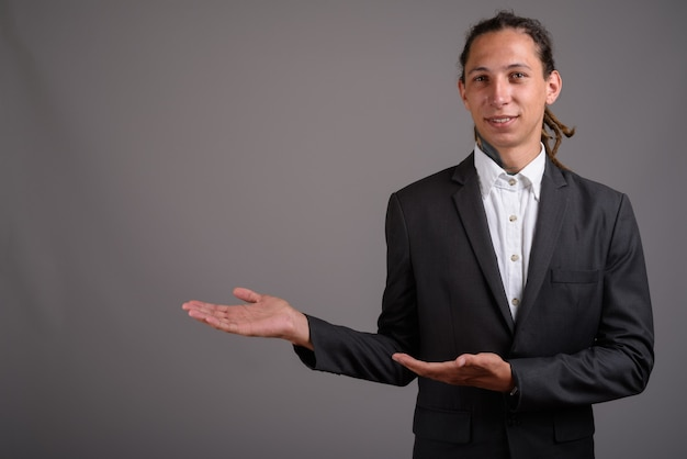 Jonge zakenman met dreadlocks tegen een grijze achtergrond