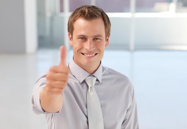 Jonge zakenman met duim omhoog naar de camera