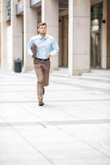 Jonge zakenman met een aktetas die in een stadsstraat loopt. haasten om te werken.