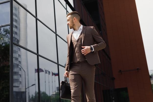 Jonge zakenman met een aktetas die in een stadsstraat loopt op een achtergrond van een modern kantoorgebouw