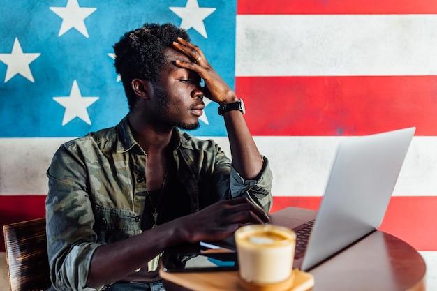 Jonge zakenman met een geschokte uitdrukking die op een laptop werkt.