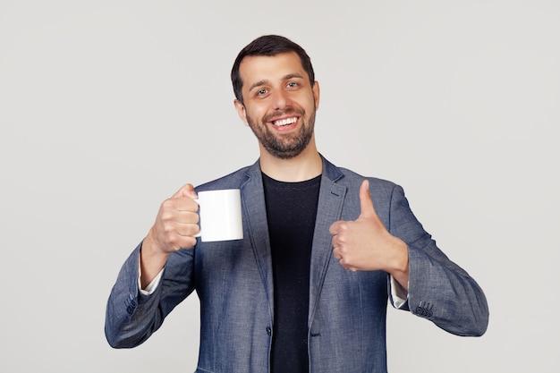 Jonge zakenman met een glimlach, een man met een baard in een jas, die een kopje koffie vasthoudt en een duim omhoog laat zien, een man met een blij gezicht.