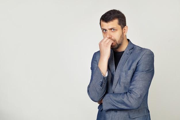 Jonge zakenman met een glimlach, een man met een baard in een jasje, ziet er gespannen en nerveus uit met de handen op zijn lippen, op zijn nagels bijtend.