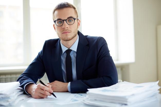 Jonge zakenman met een hoop werk