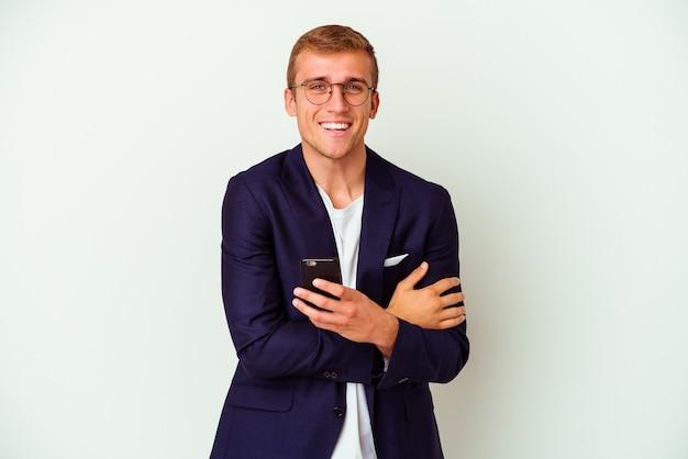 Jonge zakenman met een mobiele telefoon geïsoleerd op een witte achtergrond lachen en plezier maken.