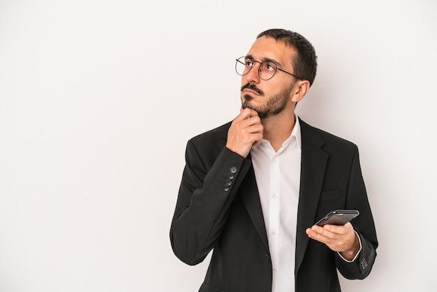 Jonge zakenman met een mobiele telefoon geïsoleerd op een witte achtergrond zijwaarts kijkend met twijfelachtige en sceptische uitdrukking.
