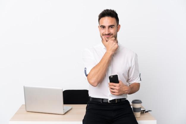Jonge zakenman met een mobiele telefoon op een werkplek lachen