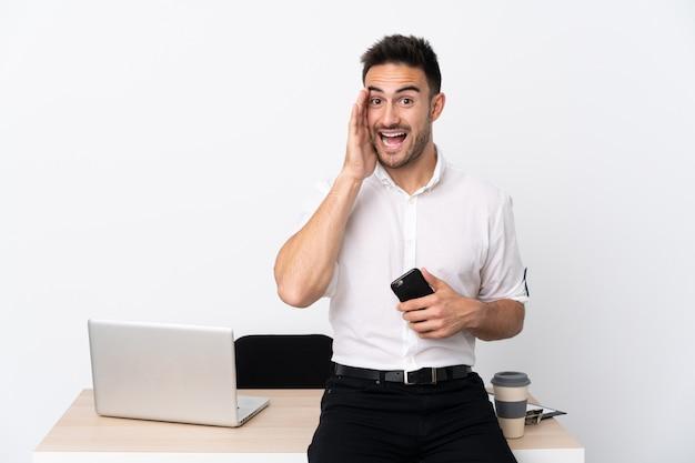 Jonge zakenman met een mobiele telefoon op een werkplek met wijd open mond schreeuwen
