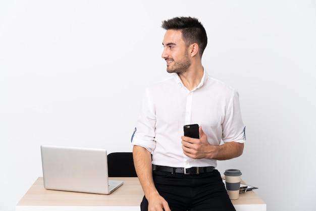 Jonge zakenman met een mobiele telefoon op een werkplek op zoek naar de kant