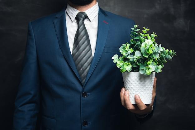 Jonge zakenman met een vaas met planten op een donkere ondergrond