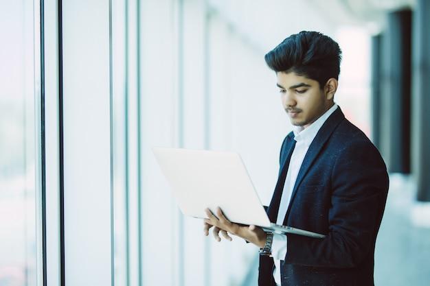 Jonge zakenman met laptop computer die op kantoor werkt